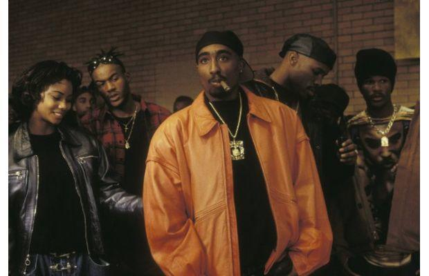 Tupac standing out in an orange leather jacket