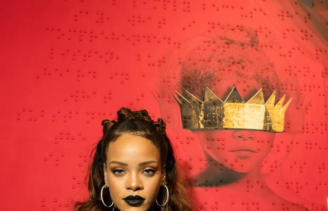 Rihanna posing in front of her 8th album cover