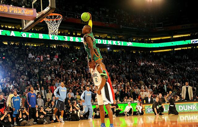 Nate Robinson of the New York Knicks leaps over Dwight Howard of the Orlando Magic in the finals of the Sprite Slam Dunk Contest on All-Star Saturday Night, part of 2009 NBA All-Star Weekend at US Airways Center on February 14, 2009 in Phoenix, Arizona